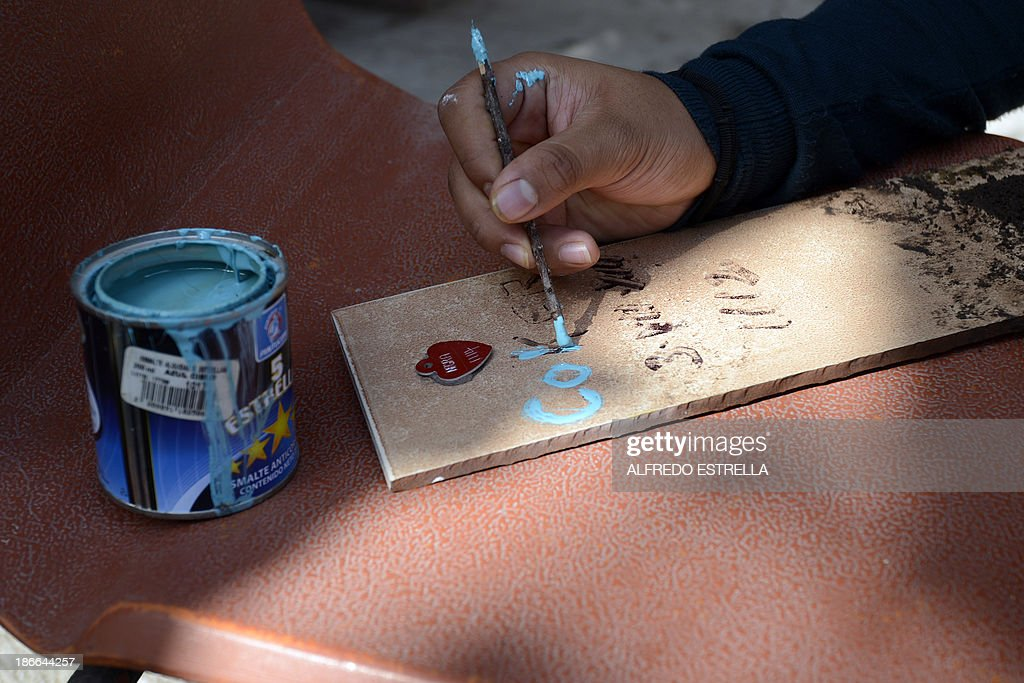 A woman paints the name of her dog's to put on its grave at the pet cemetery in Corregidora, State of Queretaro, Mexico on November 1, 2013, the day before the commemoration of the Day of the Dead. The traditional Mexican holiday honors the dead and is celebrated annually.