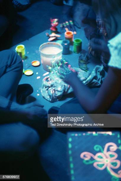 A woman paints with DayGlo colors illuminated by black light at the Avalon Ballroom San Francisco