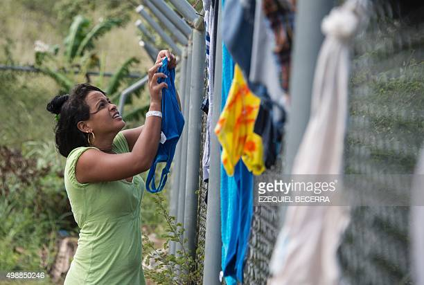 A woman part of a group of 300 Cubans who remain in a shelter hangs clothes on a fence in La Cruz Guanacaste Costa Rica near the border with...