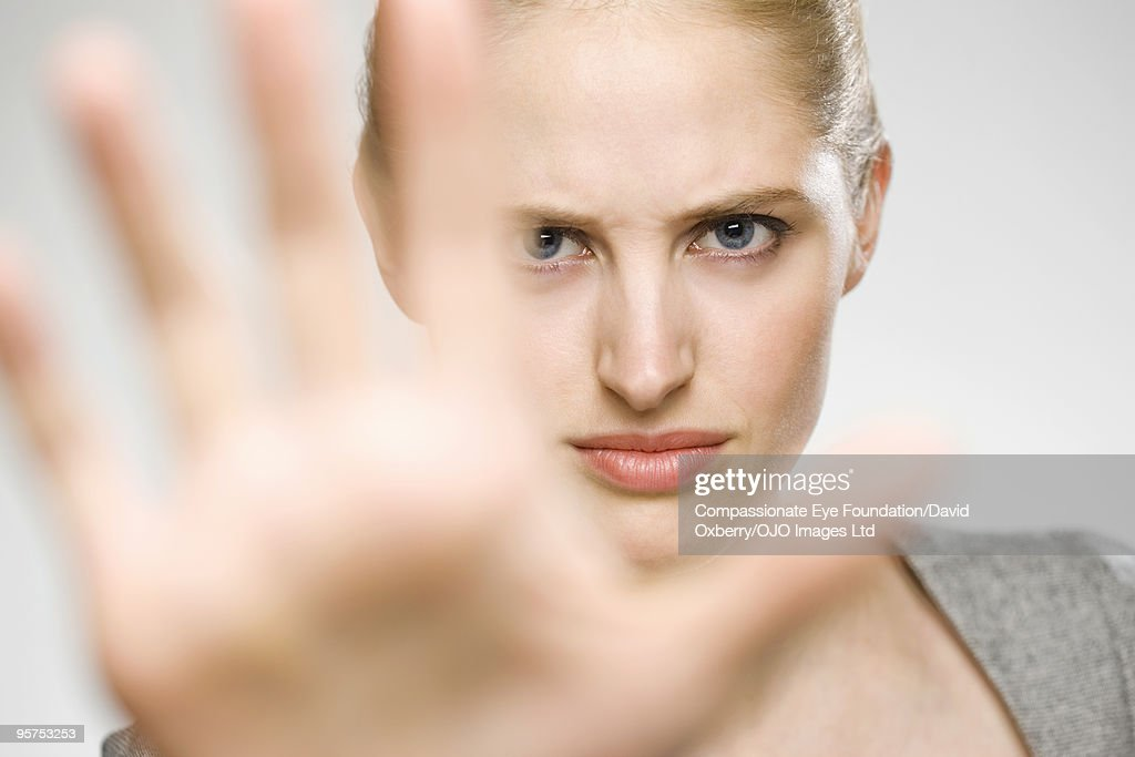 Woman partially blocking her face with her hand : Stock Photo