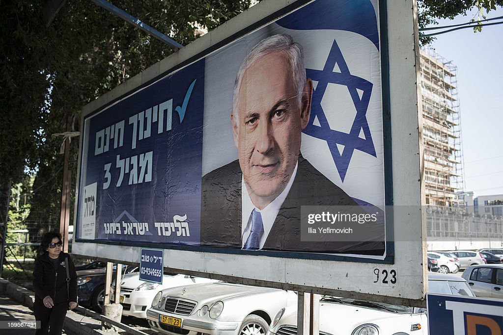 Woman pass by campaign posters of Israeli Prime Minister Benjamin Netanyahu ahead of the national elections on January 16, 2013 in Tel Aviv, Israel. General elections will be held on January 22, 2013 to decide members of parliament and whether Benjamin Netanyahu will receive another term in office at Prime Minister.