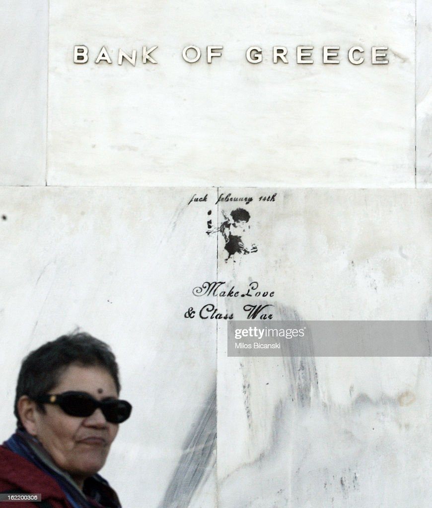 Woman pass by graffiti saying 'Make love & Class war' on enterance of Bank of Greece during a protest on February 20, 2013 in Athens, Greece. Unions have launched general strike against austerity measures in Greece, amid predictions unemployment in the crisis-hit country will reach 30 percent this year.