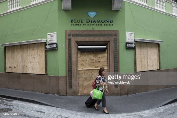 A woman passes a boarded up business as residents prepare for a direct hit from Hurricane Maria on September 19 2017 in San Juan Puerto Rico Puerto...