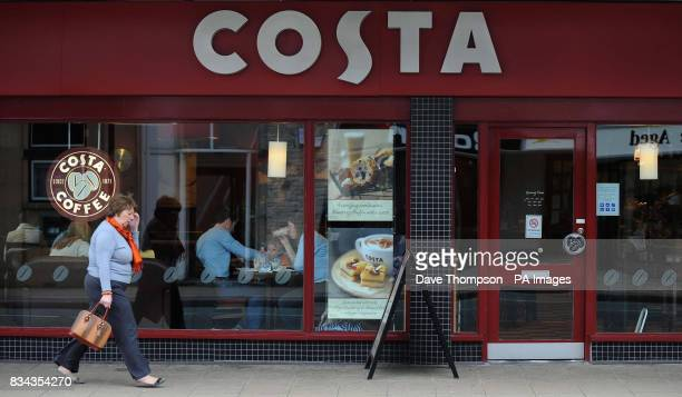 A woman passes a Costa Coffee cafe in Hale Altrincham