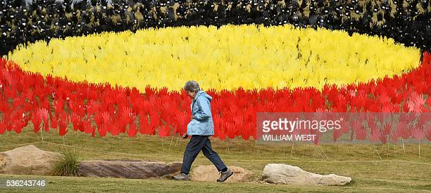 A woman passes a huge art installation called 'Sea of Hands' which consists of thousands of hands in the colours of the Aboriginal flag red yellow...