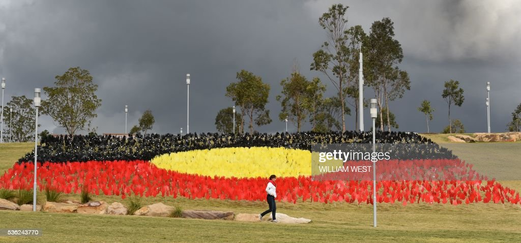 A woman passes a huge art installation called 'Sea of Hands' which consists of thousands of hands in the colours of the Aboriginal flag red, yellow, black. Part of National Reconciliation Week 2016, the installation is for Australians to reflect on Australias national identity and the place of Aboriginal and Torres Strait Islander histories and cultures in the nations story. / AFP / William WEST