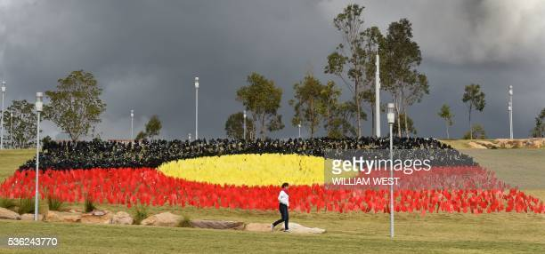TOPSHOT A woman passes a huge art installation called 'Sea of Hands' which consists of thousands of hands in the colours of the Aboriginal flag red...