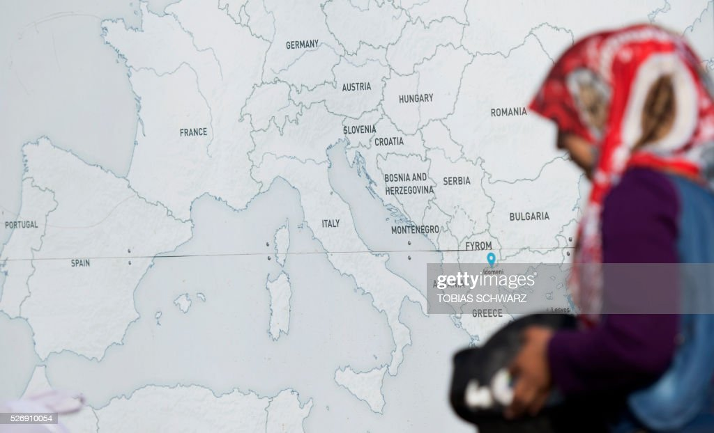 A woman passes a map at a makeshift camp for migrants and refugees near the village of Idomeni not far from the Greek-Macedonian border on May 1, 2016.Some 54,000 people, many of them fleeing the war in Syria, have been stranded on Greek territory since the closure of the migrant route through the Balkans in February. Some 54,000 people, many of them fleeing the war in Syria, have been stranded on Greek territory since the closure of the migrant route through the Balkans in February. / AFP / TOBIAS