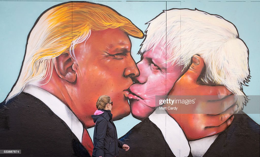 A woman passes a mural that has been painted on a derelict building in Stokes Croft showing US presidential hopeful Donald Trump sharing a kiss with former London Mayor Boris Johnson on May 24, 2016 in Bristol, England. Boris Johnson is currently one of the biggest names leading the campaign for Britain to leave the European Union in the referendum which takes place on June 23 and Republican presidential hopeful Donald Trump has also backed a so-called Brexit.