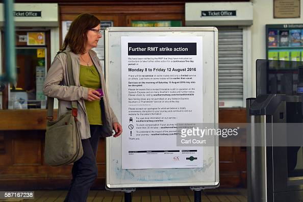 A woman passes a sign informing passengers of industrial action on the Southern rail service at Peckham Rye station on August 8 2016 in London...