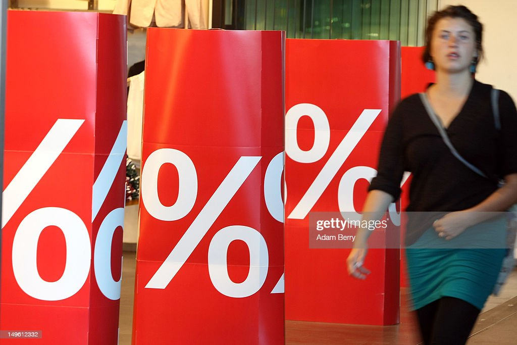 A woman passes a store advertising summer sales on August 1, 2012 in Berlin, Germany. German retailers began their annual summer clearance sale on Monday, offering deep discounts of up to 80 percent on warm weather items as they prepare to stock up for the autumn shopping season.