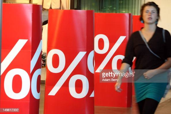 A woman passes a store advertising summer sales on August 1 2012 in Berlin Germany German retailers began their annual summer clearance sale on...