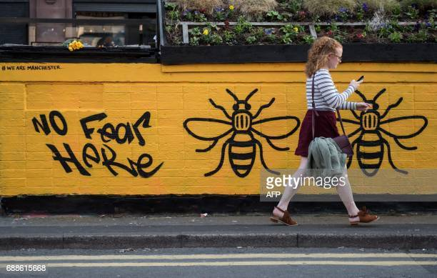 TOPSHOT A woman passes a streetart graffiti mural created following the May 22 terror attack at the Manchester Arena featuring bees which are...