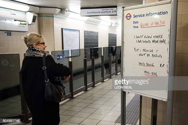 A woman passes a train Service Information board displaying lyrics by British singer David Bowie at a TFL undergound station in north London on...