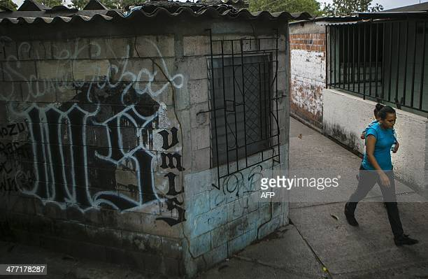 A woman passes a wall with a graffiti painted by the gang 'MS13' at Villa Mariona II in San Salvador El Salvador on March 7 prior to the second round...