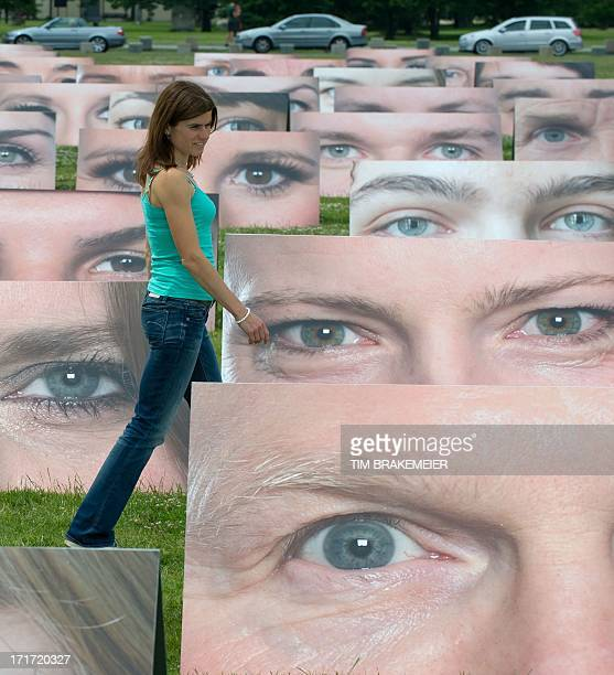 A woman passes among large format photographs of different pair of eyes displayed in front of the Reichstag building in Berlin Germany on June 28...
