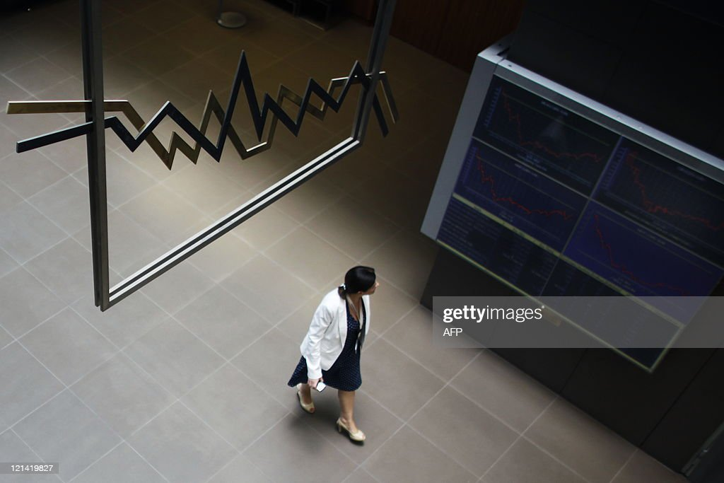 A woman passes an electronic index panel on the main entrance hall of the Hellenic Exchanges on August 9 2011 European stock exchange markets gave...