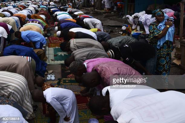 A woman passes as worshippers pray in the street for the Eid alFitr holiday on June 25 2017 in Abidjan Muslims worldwide celebrate the Eid alFitr...
