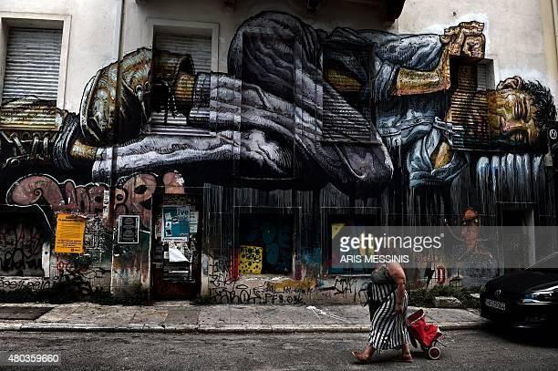 A woman passes by a graffiti depicting a homeless person in central Athens on July 11 2015 Greece's international creditors believe its latest debt...