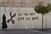 A woman passes by a graffity in central Athens on February 20 2015 Germany and Greece face off in yet another eurozone meeting Friday in search of a...