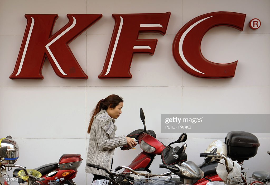 A woman passes by a Kentucky Fried Chicken (KFC) outlet in Shanghai on January 9, 2013. Chinese customers of KFC, the biggest fast food chain in the country, said they would still patronise it despite a government food safety investigation which has hit sales. US-based Yum! Brands Inc., whose portfolio includes KFC and Pizza Hut, said this week that sales in its key China market were forecast to fall more than expected in the fourth quarter in the wake of the probe into excess antibiotic levels in chickens. AFP PHOTO/Peter PARKS