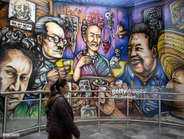 A woman passes by a mural depicting personalities related with Mexican culture at a subway station in Mexico City early on September 25 2017 almost a...