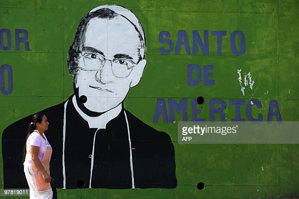 A woman passes by a mural depicting the portrait of Mons Oscar Arnulfo Romero at La Divina Providencia Hospital in San Salvador on March 17 ahead of...