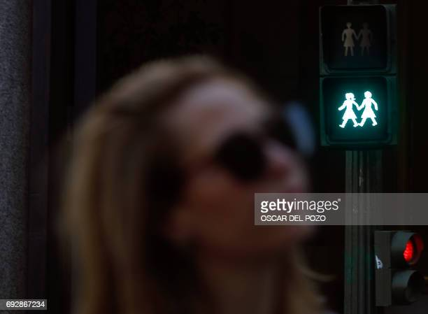 A woman passes by a new green pedestrian crossing symbol depicting a samesex couple in Madrid on June 5 2017 as Madrid will host this year's World...