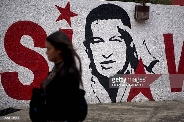 A woman passes by a wall with a graffiti depicting Venezuelan President Hugo Chavez in Caracas on October 03 2012 Elections in Venezuela will be held...