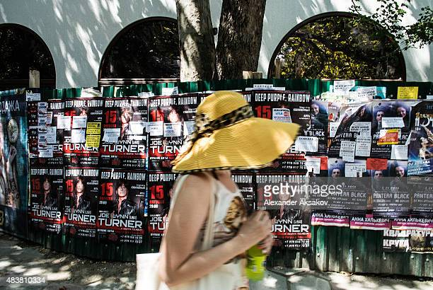 A woman passes by advertisements of coming concerts on August 11 2015 in Yalta Crimea Russian President Vladimir Putin signed a bill in March 2014 to...