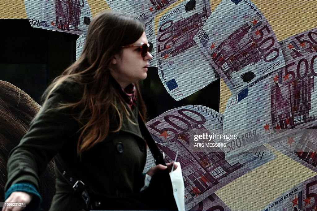 A woman passes by an advertisment with 500 euro banknotes in central Athens on January 21, 2013. AFP PHOTO / ARIS MESSINIS