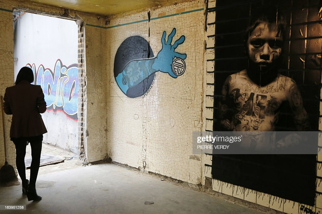 A woman passes by an artwork on March 18, 2013 during street art performances at the 'Bains-Douches' nightclub in Paris. Famous Parisian nightclub the 'Bains-Douches' was turned into a temporary artistic residence exhibiting street art works before revamp in early April to be turned into a hotel lounge by 2014. AFP PHOTO / PIERRE VERDY CAPTION