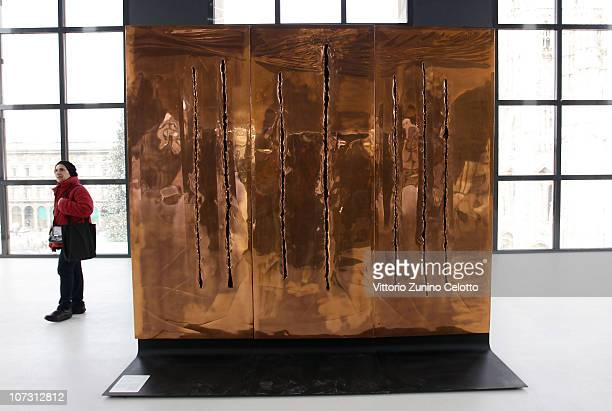 A woman passes by Concetto Spaziale by Lucio Fontana during the Museo Del Novecento press Preview on December 3 2010 in Milan Italy