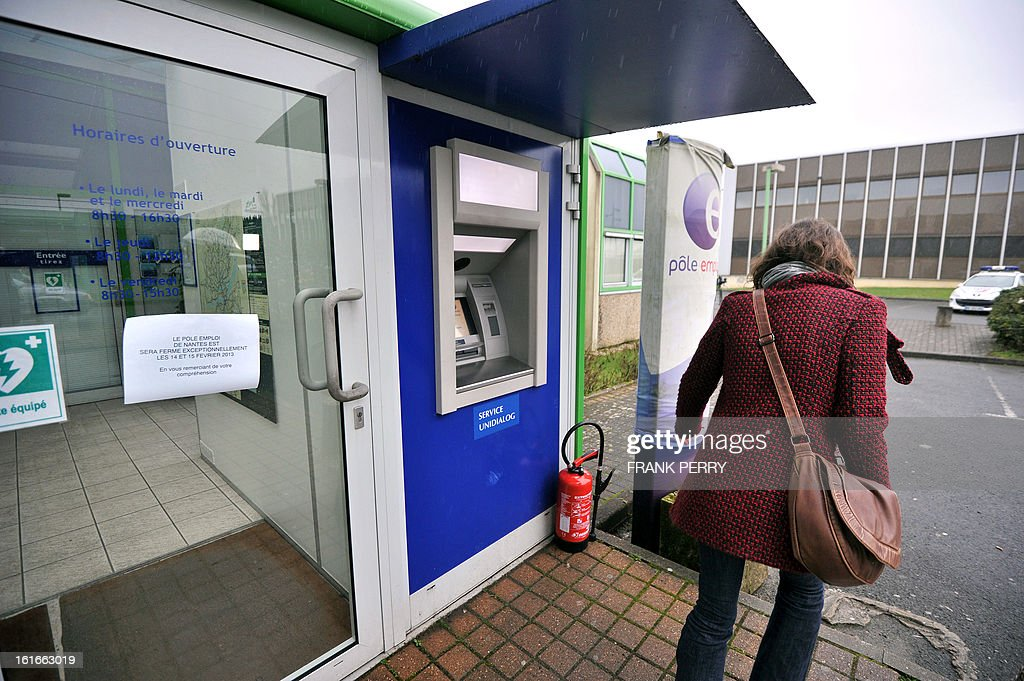 A woman passes by, on February 14, 2013 in Nantes, western France, the French employment Pole Emploi agency where a jobless man self-immolated the day before in front of the building. The agency is closed for two days following the event. The man, aged 42, reached his unemployment rights-end.
