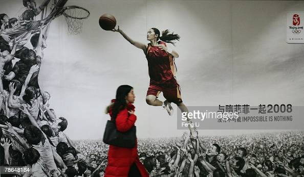A woman passes by the billboard advertising Adidas on December 26 2007 in Beijing China The Beijing Olympic Games will bring enormous commercial...