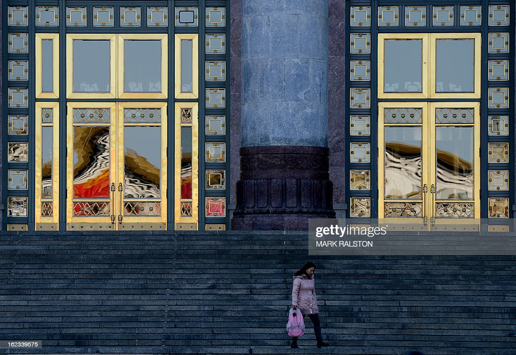 A woman passes by the doors of China's parliament building known locally as 'The Great Hall of the People' as the city prepares for news weeks legislature meetings, in Beijing on February 22, 2013. China has fixed March 5, 2013, as the date it will convene a key legislative session, state media reported Friday, with new Communist Party chief Xi Jingping set to become president during the two-week meeting. The announcement comes after the Communist Party in November chose current Vice President Xi to take over the reins of the ruling party from current President Hu Jintao. AFP PHOTO/Mark RALSTON