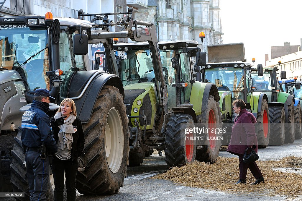 A woman (R) passes by tractors blocking the road on January 2, 2014 in Dunkerque, northern France, during a demonstration by farmers called by the Gers farmers' union FDSEA to protest against the regional and ecological key measure of the Grenelle Environment, known as 'La Trame verte et bleue' (blue-green infrastructure).