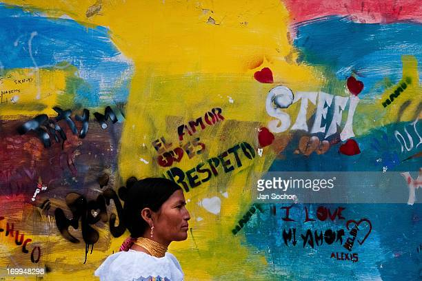"A woman passes in front of a colorfully paited wall during the Inti Raymi fiesta on 29 June 2010 in Cotacachi Ecuador Inti Raymi ""Festival of the..."