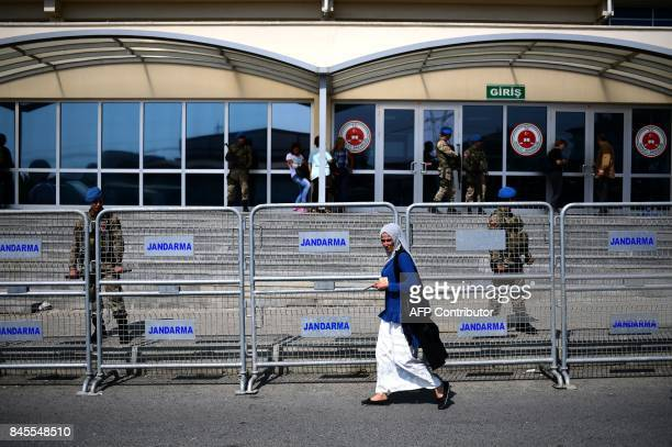 A woman passes in front of a fence as Turkish gendarmes stand guard in front of the courthouse before the controversial trial of staff from Turkey's...