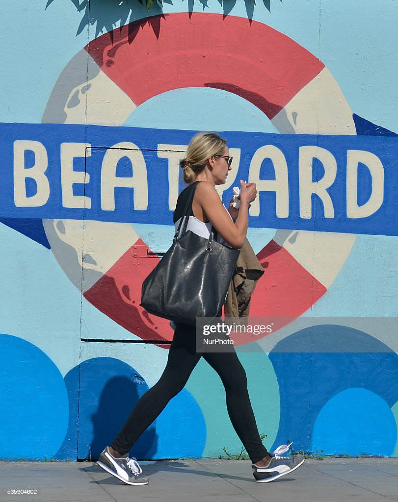A woman passes in front of a mural 'TDun Laoghaire Harbour' advertising The Beatyard - a Dublin City Festival. On Monday, 30 May 2016, in Dublin, Ireland.