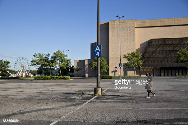 A woman passes in front of a shuttered anchor store in the parking lot of the Marley Station Mall during the Dreamland Amusements carnival in Glen...