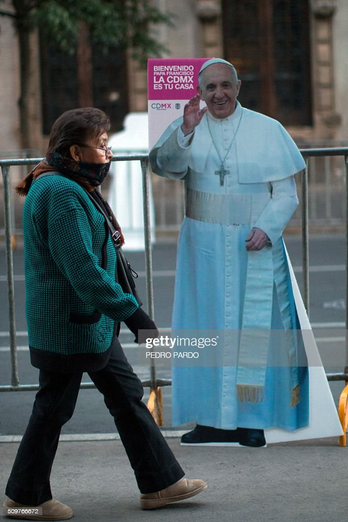 A woman passes in front of an image of Pope Francis, in Mexico City on February 12, 2016 hours before the arrival of the pontiff to the country. Pope Francis left Rome on Friday bound for Cuba, where he is to hold a historic meeting Russian Patriarch Kirill before continuing on to Mexico for a five-day visit. AFP PHOTO / Pedro PARDO / AFP / Pedro PARDO
