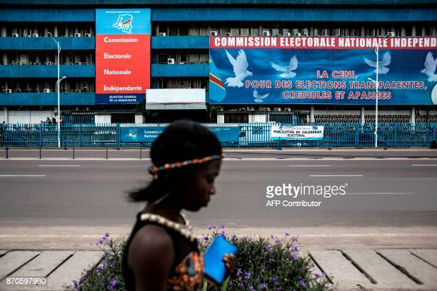 A woman passes in front of the Commission Electorale Nationale Independante headquarters on November 5 2017 in Kinshasa following an announcement of...