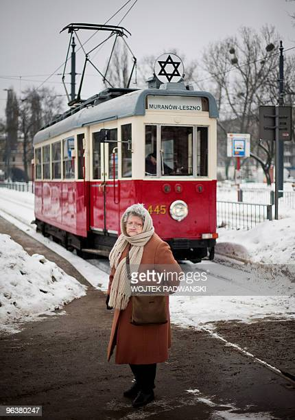A woman passes in front of the historic empty tram marked with the Star of David which rolls every year through the streets of the Polish capital in...