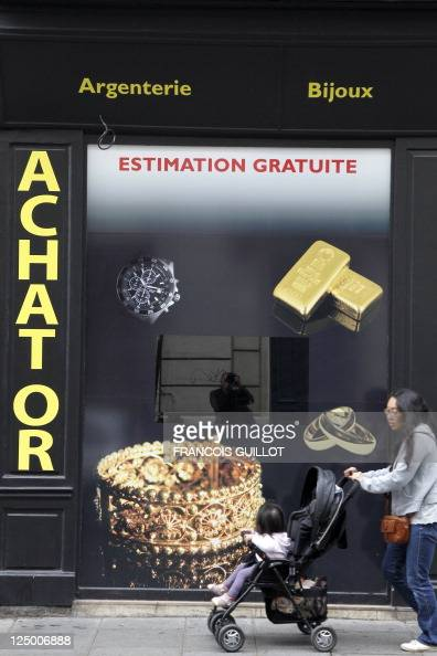 A woman passes in front of the window of a shop that buys sales and estimates gold and jewllery on September 8 2011 in Paris AFP PHOTO FRANCOIS...