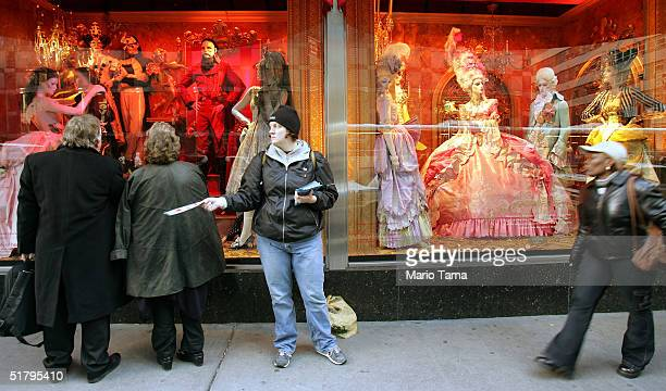 A woman passes out fliers in front of the Bloomingdale's holiday window display November 26 2004 in New York City The Friday after Thanksgiving...