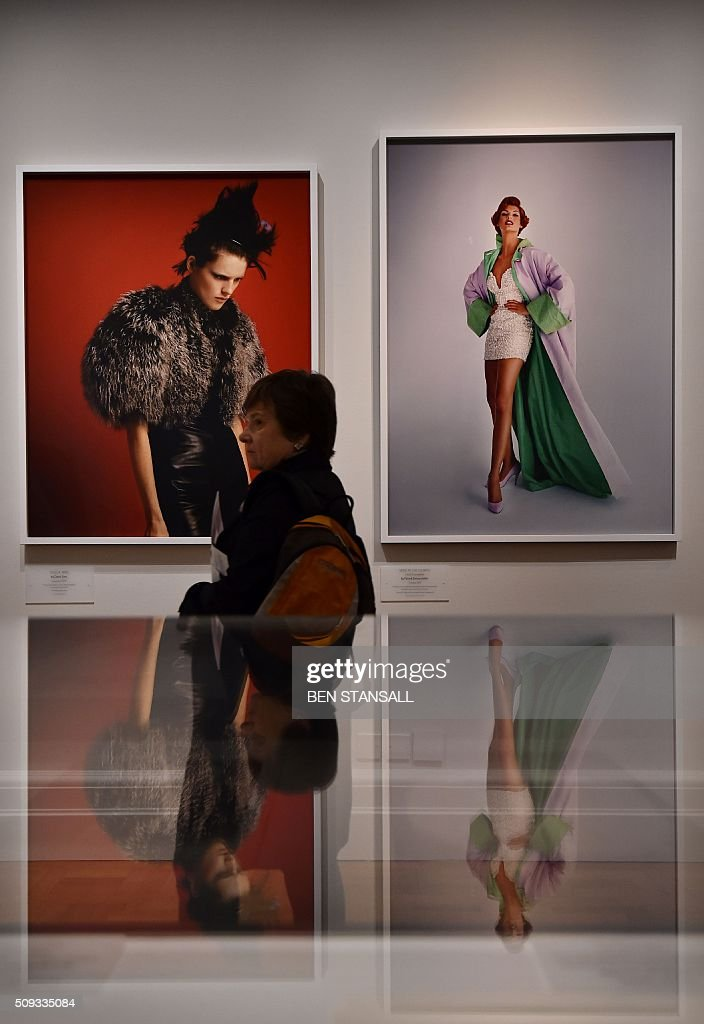 A woman passes photographs by Patrick Demarchelier 'Send in the Gowns' 1991 (R) and David Sims' 'Stella, 1995' as part of the 'Vogue 100 a Century of Style' exhibition at the National Portrait Galley in central London on February 10, 2016. The exhibition showcases a range of photography commissioned by British Vogue since it was founded in 1916. / AFP / BEN STANSALL / RESTRICTED TO EDITORIAL USE - MANDATORY MENTION OF THE ARTIST UPON PUBLICATION - TO ILLUSTRATE THE EVENT AS SPECIFIED IN THE CAPTION