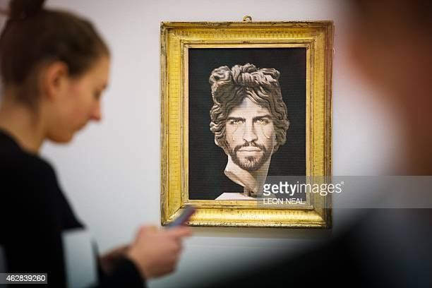 A woman passes 'Portrait of Gerard Pique as Apollo del Belvedere' by Francesco Vezzoli with an estimate of £3000040 during a press preview in central...
