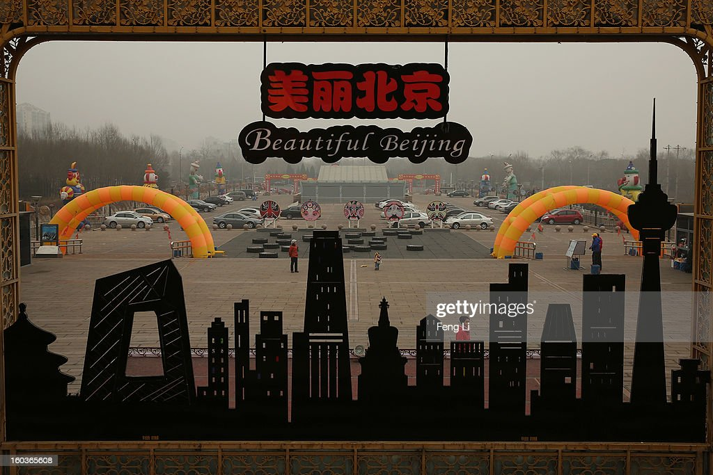A woman passes the billboard with Beijing's landmark building during severe pollution on January 30, 2013 in Beijing, China. The fourth round of heavy smog to hit Beijing in one month has sent more people to the hospital with respiratory illnesses and prompted calls for legislation to curb pollution. The haze choking many Chinese cities covers a total area of 1.3 million square kilometers, the China's Ministry of Environmental Protection said Tuesday.