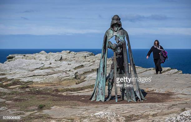 A woman passes the new 'Gallos' sculpture that has been erected at Tintagel Castle in Tintagel on April 28 2016 in Cornwall England The English...